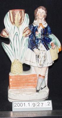 Figurine of a woman beside flower vase