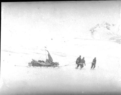 Lantern slide: Three men hauling loaded sledge fitted with sail