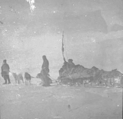 Lantern slide: Loaded sledge being hauled by men and dogs