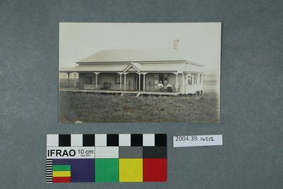 Postcard: Man and woman seated on porch of a house