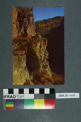 Postcard of a van driving along a cliff face