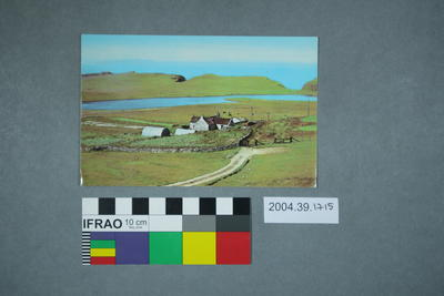 Postcard of a house in a field next to water
