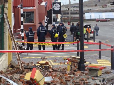 Digital Photograph:  Earthquake damage on corner of Canterbury and London Streets, Lyttelton with sailors standing on street