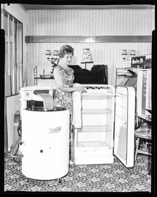 Film negative: Woman with Beatty washing machine and dryer cabinet