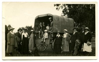 Photograph, Black and White: Lovell-Smith family group standing beside a covered wagon.