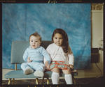 Negative: Two Children Sitting On Chairs